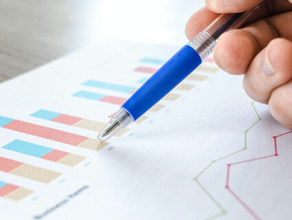 close up of man holding pen pointing at graph on paper